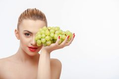 Attractive young woman with green fresh grape Stock Photos