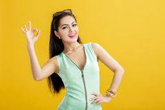 Attractive young woman in green swimsuit on yellow background. summer sexy girl in turquoise bodysuit showing OK sign Royalty Free Stock Image
