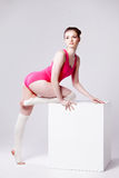 Attractive young woman gymnast on white cube Royalty Free Stock Photos