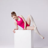 Attractive young woman gymnast on  white cube Stock Photos