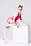 Attractive young woman gymnast on  white cube, in Stock Image