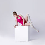 Attractive young woman gymnast on a white cube Stock Image