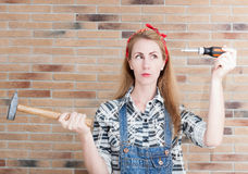 Attractive young woman with a hammer and a screwdriver Royalty Free Stock Image