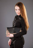 Attractive young woman with a handbag. On grey background Stock Photo