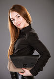 Attractive young woman with a handbag. On grey background Stock Photos