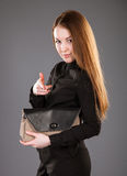 Attractive young woman with a handbag. Indicating the something on grey background Royalty Free Stock Photos