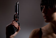 Attractive young woman with handgun Royalty Free Stock Photos