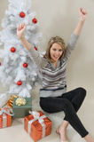 An attractive young woman happy to receive a gift on Christmas m Royalty Free Stock Photos