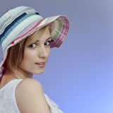 Attractive young woman in hat. Portrait of attractive young blond woman in colorful hat looking over shoulder, blue studio background with copy space Royalty Free Stock Photo