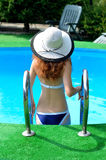 Attractive young woman in a hat down in the pool, summer photo. A slender woman in a bikini Stock Photography