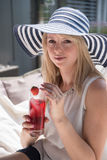 Attractive young woman with hat on and drink.  Royalty Free Stock Photo