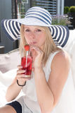 Attractive young woman with hat on and drink.  Stock Photo