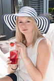 Attractive young woman with hat on and drink.  Royalty Free Stock Image