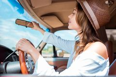 Attractive young woman in hat driving car during. Road trip royalty free stock photography