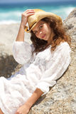 Attractive young woman with hat leaning against rock at the beach Royalty Free Stock Images
