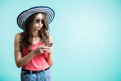 Attractive young woman in the hat looking at her smart phone and reads the message with serious faces. Technology, communication, people concept Stock Images