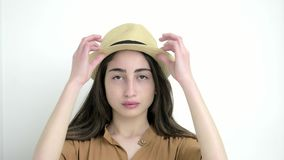 Attractive young woman in the hat looking to the camera corrects hairstyles on the white background. Close up. Portrait shot stock video