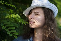 Attractive young woman in a hat looks through the branches of a tree Stock Photography