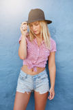 Attractive young woman with hat. Portrait of attractive young woman with hat standing against blue wall. Caucasian female model in stylish casual wear Stock Image