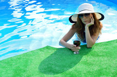 Attractive young woman in a hat and sunglasses on the edge of th. E pool, space for text. Sexy young woman in a hat with a wine glass Stock Photo