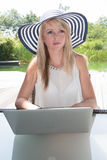 Attractive young woman with hat working on laptop.  Royalty Free Stock Photo