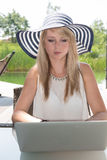 Attractive young woman with hat working on laptop.  Royalty Free Stock Photos