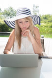 Attractive young woman with hat working on laptop.  Stock Photography