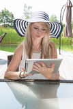 Attractive young woman with hat working on tablet.  Stock Image