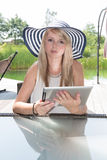 Attractive young woman with hat working on tablet Royalty Free Stock Photography
