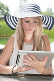 Attractive young woman with hat working on tablet Stock Images