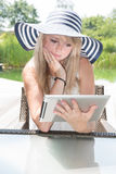 Attractive young woman with hat working on tablet. Attractive young woman with hat working on laptop Stock Image