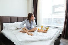 Attractive young woman having breakfast in bed in hotel Stock Images