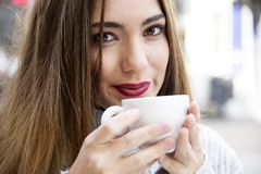 Attractive young woman is having a coffee on a street with street life background in autumn time. Royalty Free Stock Photo