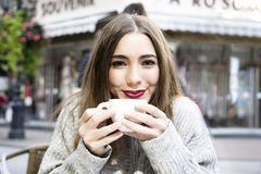 Attractive young woman is having a coffee on a street with street life background in autumn time. Royalty Free Stock Photos