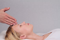 Attractive young woman having reiki healing treatment , alternative  medicine concept. Royalty Free Stock Photo