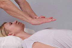 Attractive young woman having reiki healing treatment , alternative  medicine concept. Royalty Free Stock Images