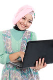 Attractive young woman in head scraf using laptop Stock Image