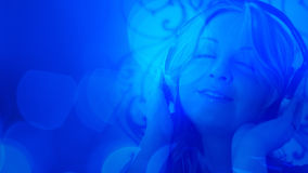 Attractive young woman with headphones blue abstract background Royalty Free Stock Images