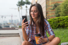 Attractive young woman in headphones listening to music using a smartphone and drinking coffee while sitting on curb Stock Images