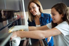 Attractive young woman with her little cute daughter cooking cookies on kitchen at home stock photography