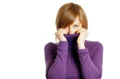 Attractive young woman hiding in the turtleneck. Isolated over white Stock Photo