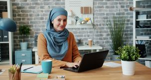 Attractive woman in hijab working in office with laptop then looking at camera. Attractive young woman in hijab is working in loft style office with laptop then stock footage