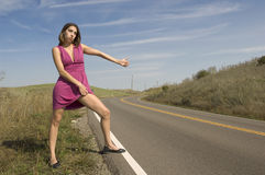 Attractive young woman hitch hiking Royalty Free Stock Photos
