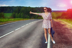 Attractive young woman hitchhiking along a road. Stock Photos
