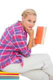 Attractive young woman holding a book and sitting on a stack of books Stock Image