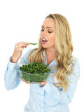 Attractive Young Woman Holding a Bowl of Freshly Cooked Green French Beans Eating One. Attractive young, blonde haired woman, in her twenties, holding a glass Royalty Free Stock Image