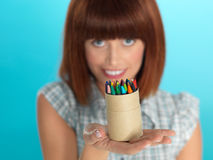Attractive young woman holding box of crayons Royalty Free Stock Images