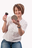Attractive young woman holding a brush and mirror in her hands,. Getting ready for going out Stock Image
