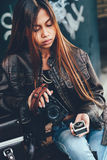 Attractive young woman holding camera and light meter in her hands in a fashionable style. Attractive young woman holding camera and light meter in her hands Stock Photo