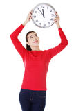 Attractive young woman holding a clock. Stock Photos